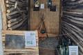 Dziwaczne wystawa  w Laboratorium: okop z kociołkiem, butelkami i tablicą grobową
